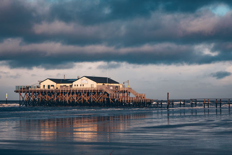 Pier over sea by houses against sky
