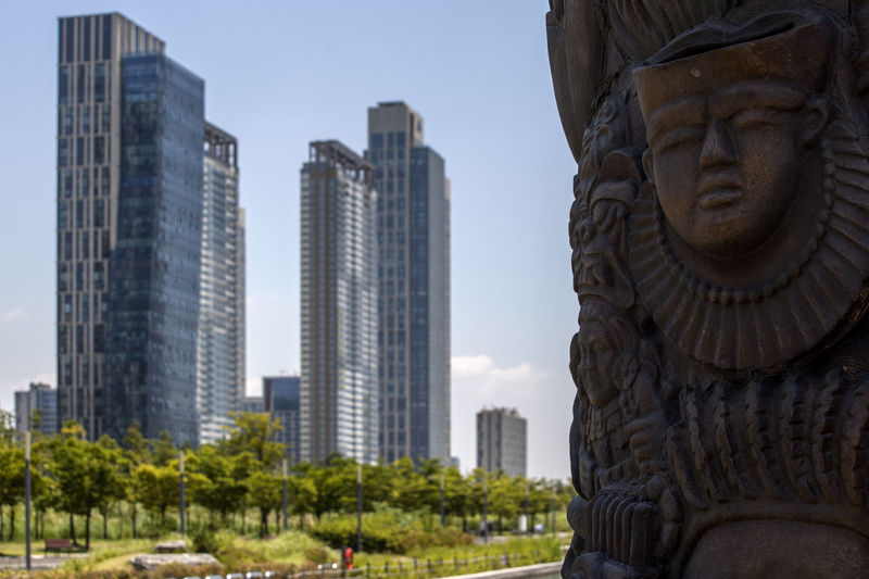 Carved wooden sculpture with modern buildings in background