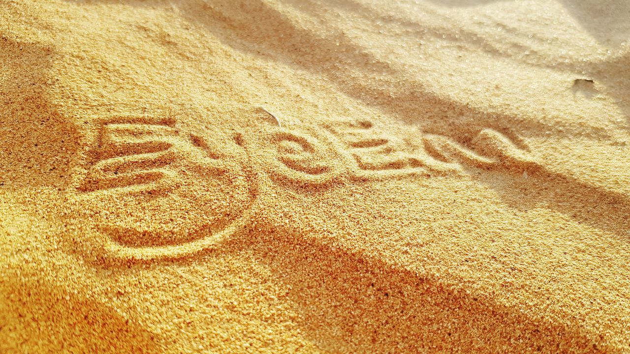 CLOSE-UP OF TEXT ON SAND AT BEACH