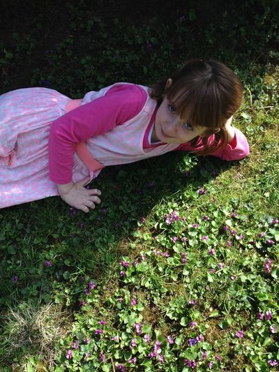 High Angle Portrait Of Girl Lying On Field At Park