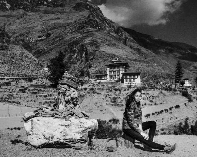 Side view of woman sitting on rock against building