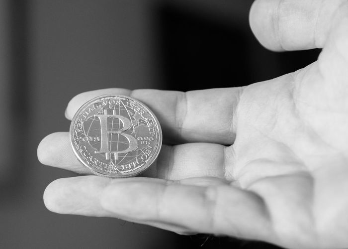 A minted Bitcoin in silver close up in hand black and white. Banking Bitcoin Black And White Close-up Coin Cryptocurrency Day Digital Digital Currency Fingers Future Holding Human Body Part Human Hand Indoors  Investing Management Minted One Person People Quarter  Real People Silver  Technology Wealth