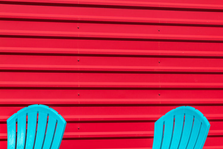 Blue chairs in front of red wall