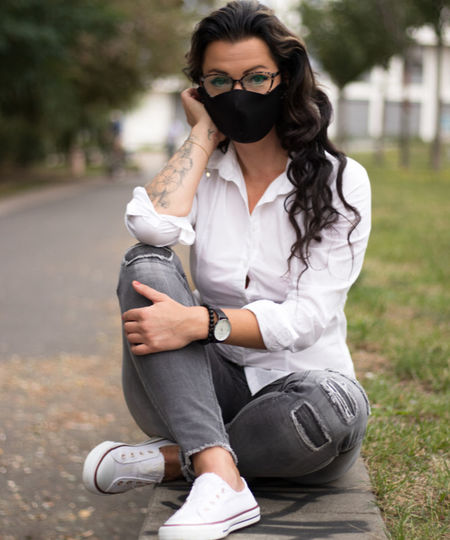 Portrait of woman wearing mask and sitting outdoors
