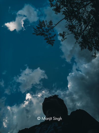 Low angle view of silhouette man against sky