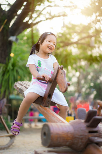 Asian little girl having fun on seesaw at playground Happiness Casual Clothing Child Childhood Cute Emotion Enjoyment Females Focus On Foreground Full Length Girls Happiness Innocence Leisure Activity Lifestyles Little Girl One Person Outdoors Portrait Real People Riding Seesaw Sitting Smiling Women