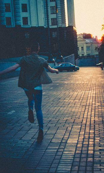 Blue jeans, black shoes, blonde hair. Kyiv Grushevskogo Street Summer Sunset