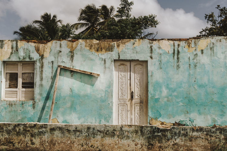 turquoise colored front of weathered house in Marajo, Brazil Architecture Built Structure Building Exterior Building Door Entrance Tree Plant House No People Old Day Sky Weathered Cloud - Sky Abandoned Residential District Nature Run-down Outdoors Turquoise Colored Ruined Front View Weathered