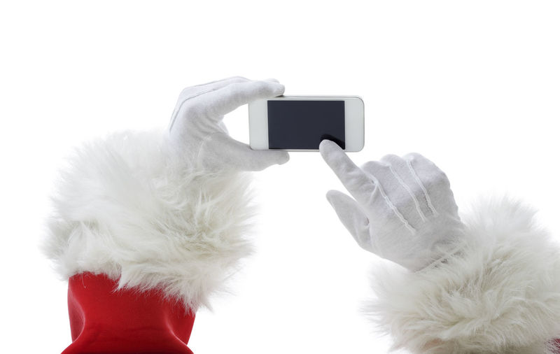Close-up of hand holding camera with mobile phone against white background