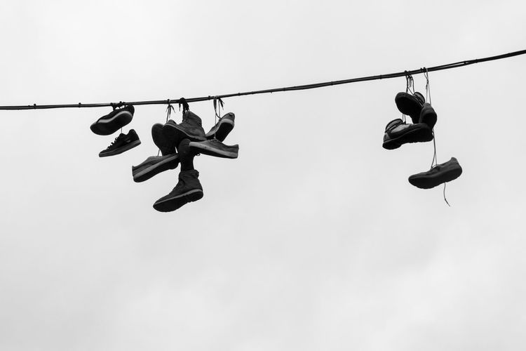 Low Angle View Of Abandoned Shoes Hanging From Cable Against Sky