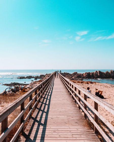 View of wooden footbridge leading towards sea against sky