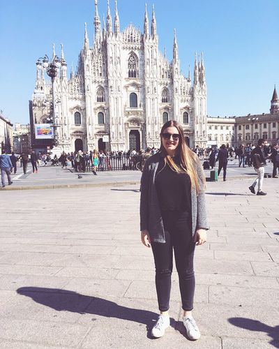 Full length portrait of happy woman standing against duomo di milano