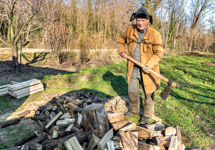 Portrait of smiling senior man with axe standing by logs at field