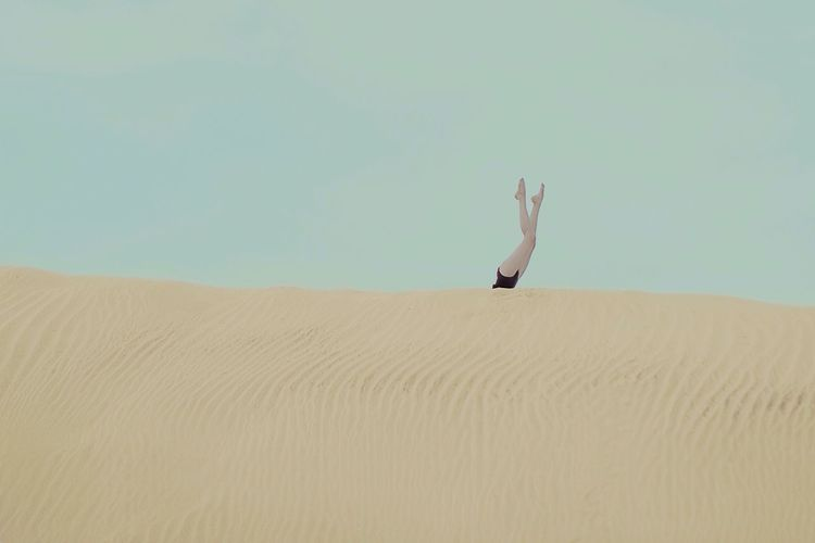 Woman with legs raised on sand dune