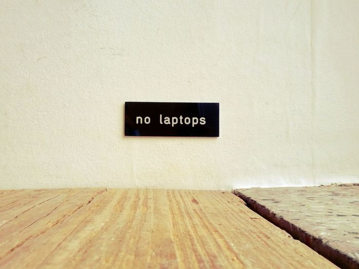 No laptops sign on wall