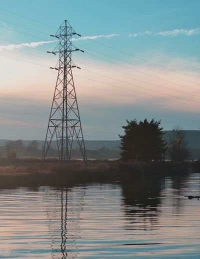 Electricity pylon by lake against sky during sunset