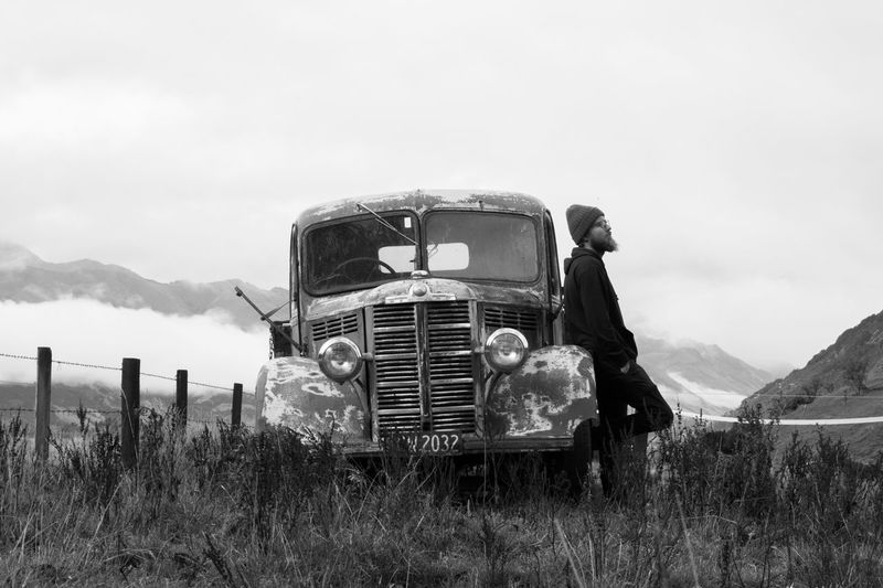 Man Leaning Against Abandoned Truck On Field