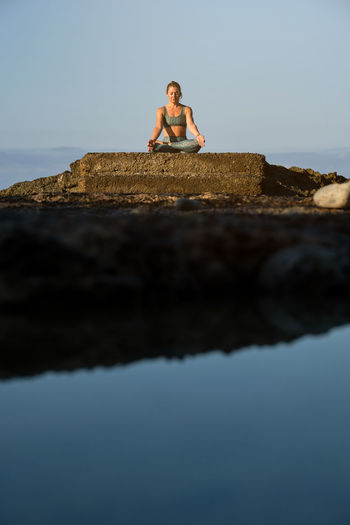 Young woman sitting on rock against sky