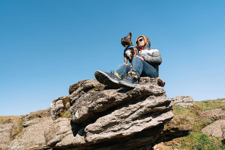 Low angle view of men on rock against clear blue sky
