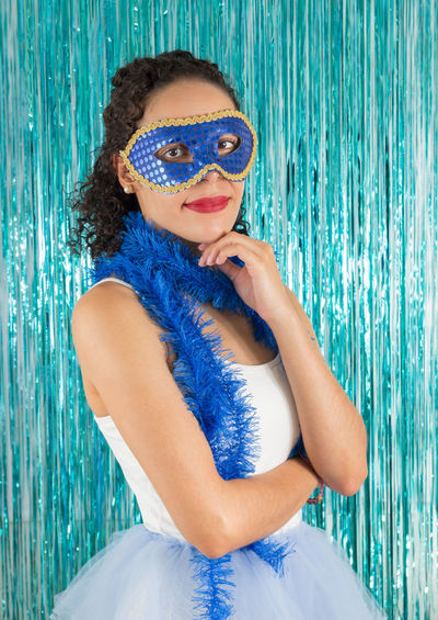 Portrait of young woman wearing feather boa and mask while standing against decorations