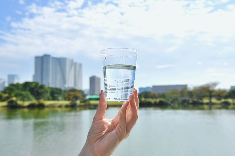 Water Holding Human Hand Hand Human Body Part Nature Sky Lake Glass Drinking Glass Focus On Foreground Plant Outdoors Drink Refreshment Finger Clear Water Environment Earth City Life Save The Nature Chemical Contamination Water Supply