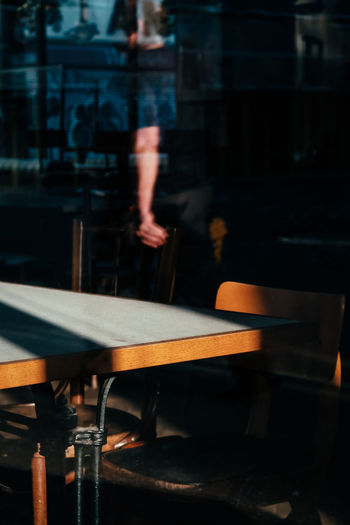 Blurred motion of man standing by table at cafe
