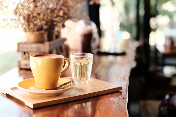 Yellow cup of Hot coffee in break time at cafe , film look effect image tone. Table Food And Drink Drink Coffee - Drink Refreshment Coffee Coffee Cup Mug Cup Latte Cafe Focus On Foreground Indoors  Coffee Shop