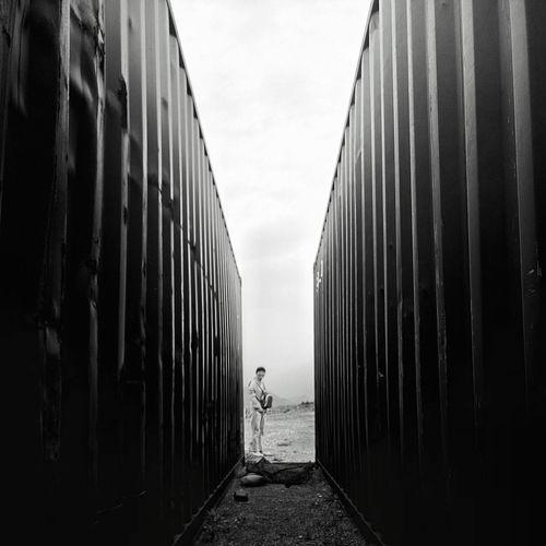 Person Seen Through Cargo Containers