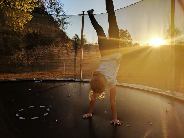 Trampoline Sunset Sun Sunlight Lens Flare Sky One Person Girl Tree Reflection
