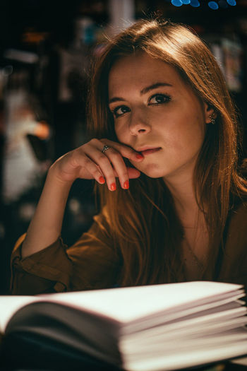 Portrait of beautiful young woman reading book