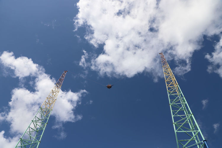 Low angle view of thrill seekers on amusement park bungee ride