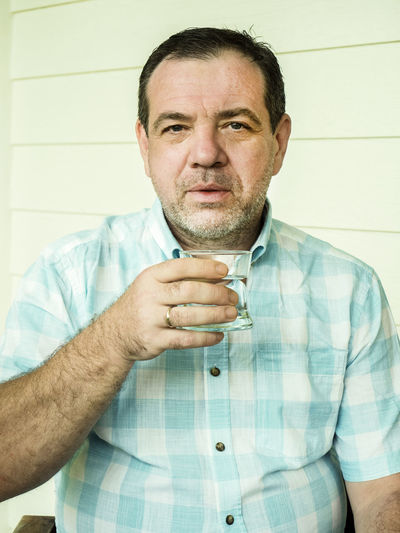 Portrait of man holding coffee cup while sitting against wall