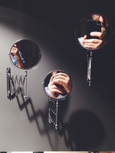 Reflection of man on mirror while photographing using mobile phone