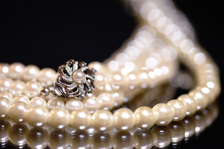 Close-Up Of Pearl Necklace With Pendant Against Black Background