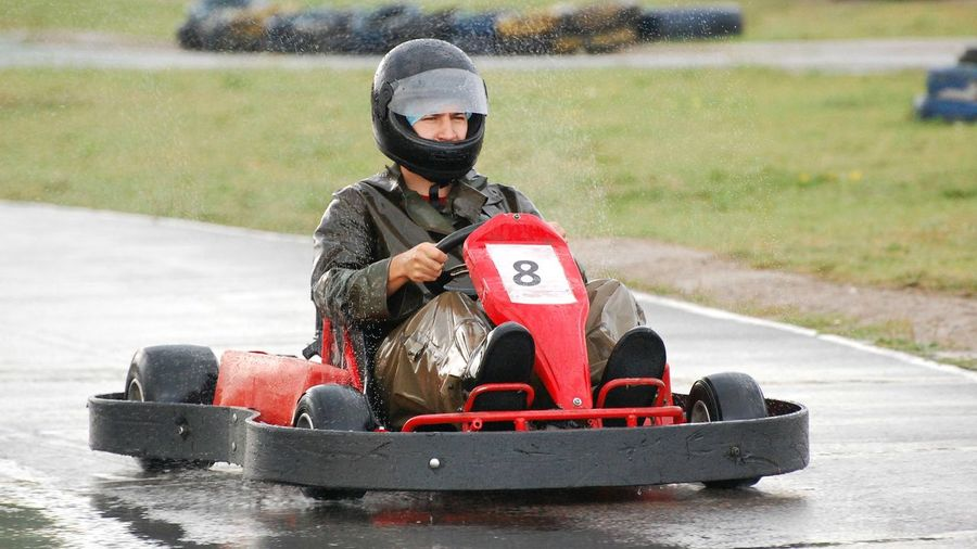 Man driving racecar on wet motor racing track