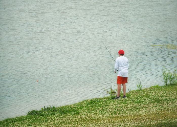 Rear view of man fishing on shore