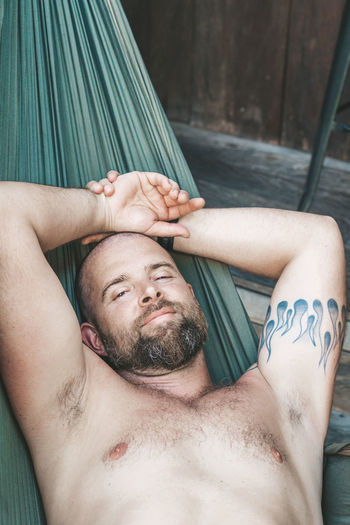 Relaxing in a hammock Shirtless Lying Down Real People Tattoo Young Adult Beard Lifestyles One Person Front View Portrait Relaxation Men Lying On Back Young Men Facial Hair Headshot Eyes Closed  Adult Hands Behind Head Human Arm Human Limb