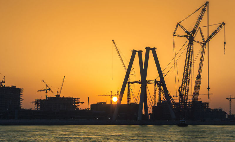 The Silhouette Sunset Crane - Construction Machinery Water Orange Color Industry Silhouette Business Finance And Industry No People Sea Sky Commercial Dock Nature Oil Pump Steel Travel Destinations Day Outdoors EyeEm Ready
