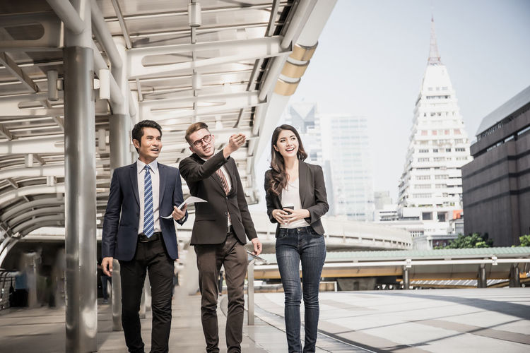 Adult Architecture Building Exterior Built Structure Business Person Businessman City Coworker Front View Looking At Camera Males  Men Office Real People Standing Three Quarter Length Well-dressed Women Young Adult Young Men