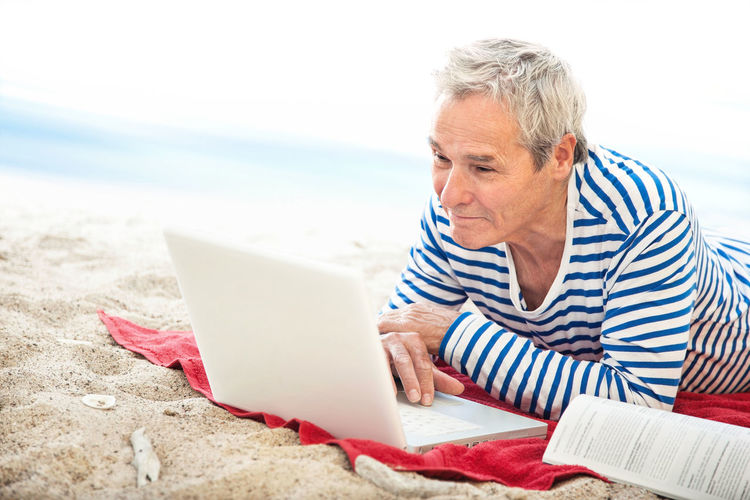 Close-up of man using laptop on beach