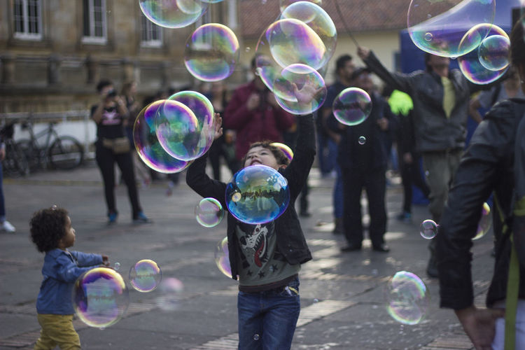 People with bubbles on street in city