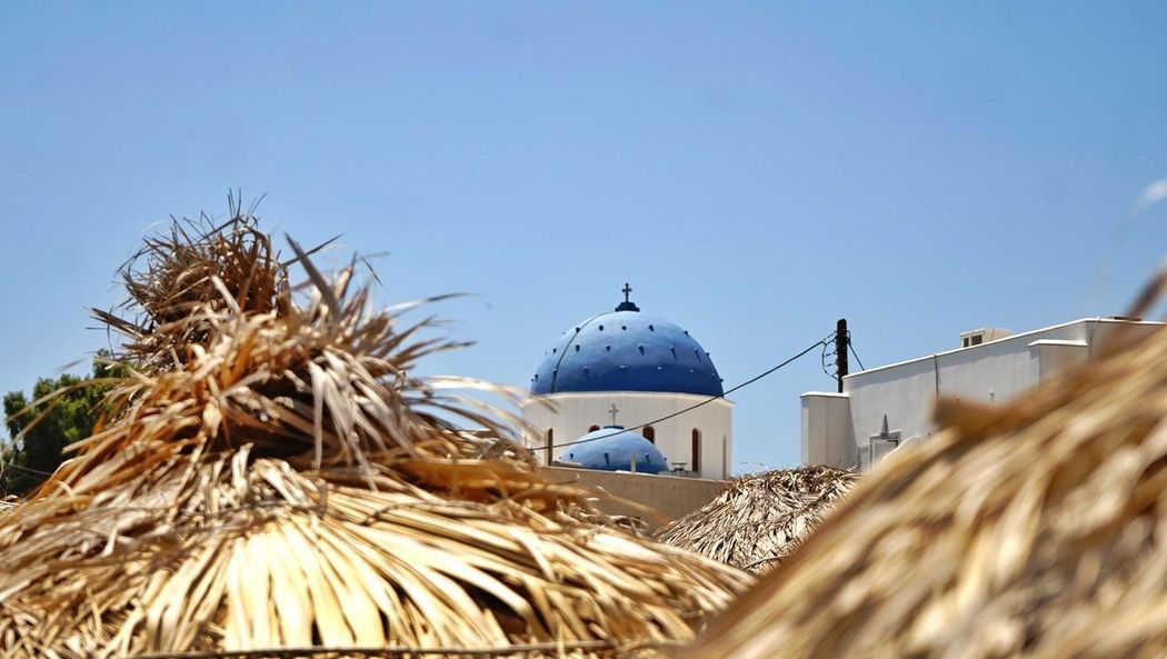 View from the beach (Santorini). Beach Church Architecture Church Beach Parasols Blue Sky Santorini Santorini, Greece Dome Clear Sky Place Of Worship Blue Religion Tree Sky Architecture Sandy Beach Beach Umbrella Historic Whitewashed