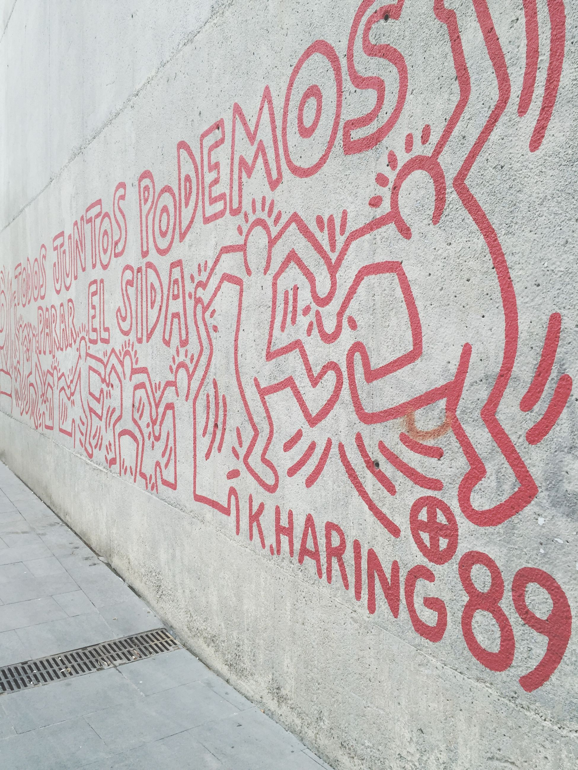 wall - building feature, text, architecture, built structure, graffiti, art, art and craft, creativity, western script, street, communication, red, building exterior, pattern, wall, sidewalk, outdoors, day, textured, cobblestone
