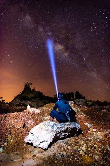 Rear view of man with illuminated flashlight sitting on rock at night