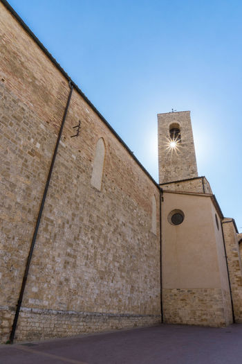San Gimignano Tuscany Against The Sun Architecture Belief Blue Building Building Exterior Built Structure Clear Sky Clock Copy Space Day History Italy Low Angle View Nature No People Outdoors Place Of Worship Religion Sky Spirituality Sunstar Tower