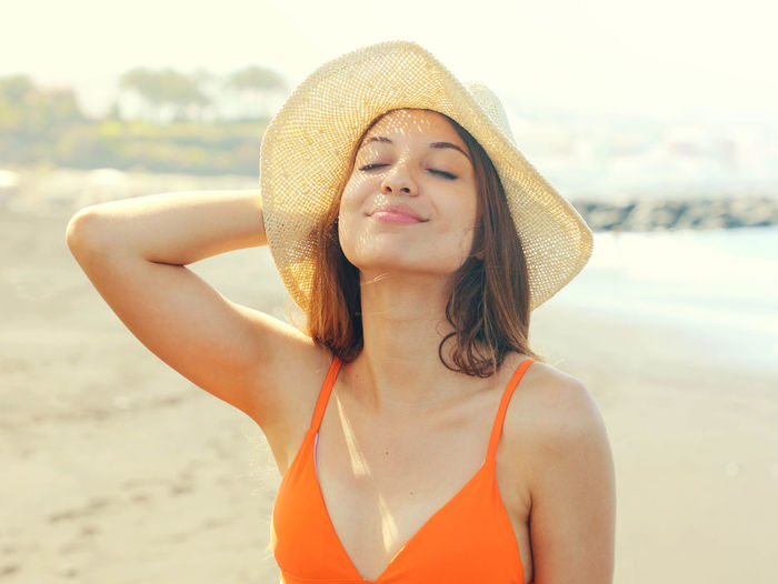Close-up of woman wearing hat while standing at beach
