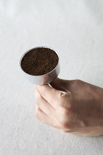 Cropped Image Of Hand Holding Ground Coffee In Container At Table