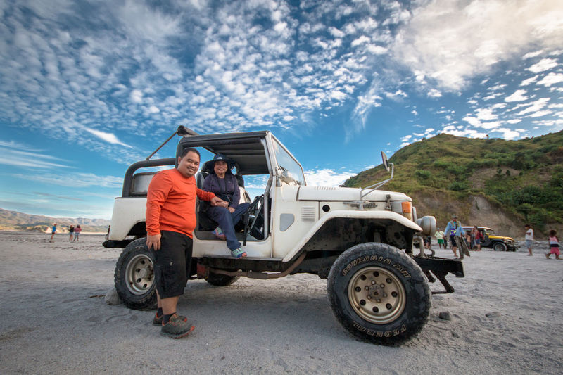 Travelling on rough terrain Transportation Two People Adults Only People Sky Day Outdoors Standing Togetherness Young Adult Portrait Commercial Travel Rough Road Adventure Adventure Buddies 4x4 Travel Jeep Land Cruiser Let's Go. Together.