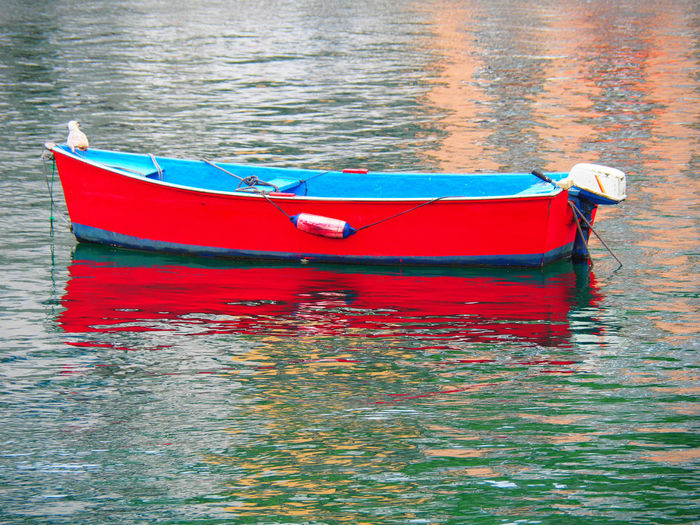 Red boat moored in lake
