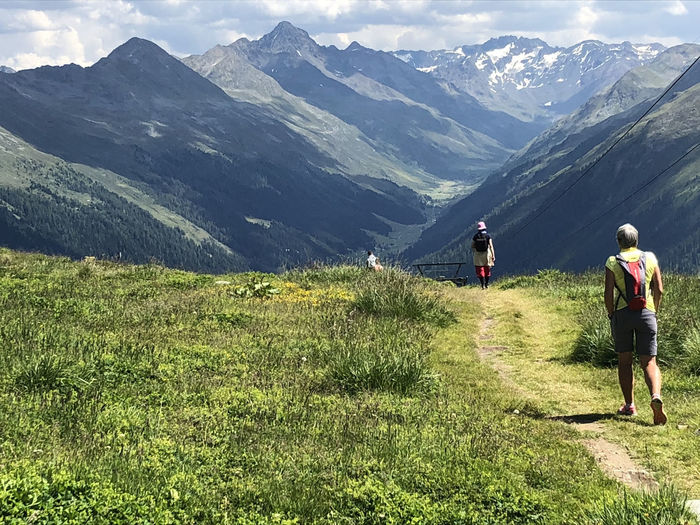 Mountain path Activity Day Grass Green Color Hiking Leisure Activity Mountain Mountain Path Mountain Range Mountains And Valleys Outdoors People Rear View Scenics - Nature Tranquil Scene Tranquility Walking